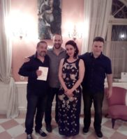 "Sasha with friends on the opening night in front of her painting ""medico della peste umana"""